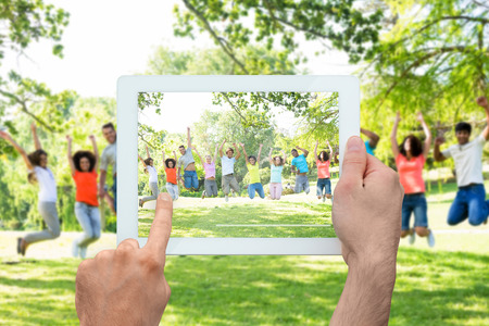 Hand holding tablet pc showing cheerful friends jumping  photo