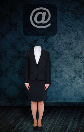 Composite image of headless businesswoman with at sign against dark grimy room photo