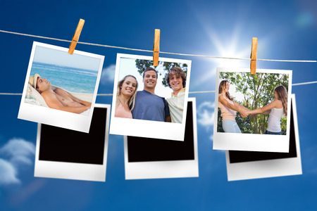 Composite image of instant photos hanging on a line against blue sky photo