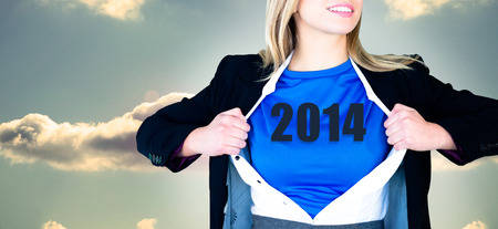 Businesswoman opening her shirt superhero style against bright blue sky with cloud photo