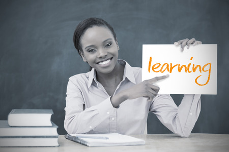 Happy teacher holding page showing learning in her classroom at school photo