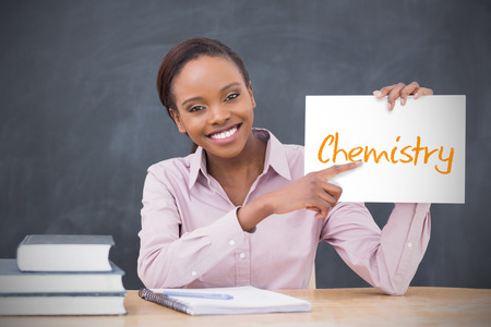 Happy teacher holding page showing chemistry in her classroom at school photo