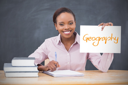 Happy teacher holding page showing geography in her classroom at school photo
