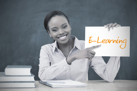 Happy teacher holding page showing e learning in her classroom at school photo
