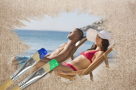 Composite image of couple lying on the beach with paintbrushes against weathered surface  photo