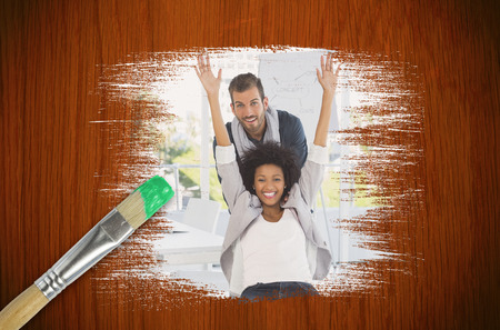 Composite image of colleagues having fun with paintbrush dipped in green against wooden oak table photo