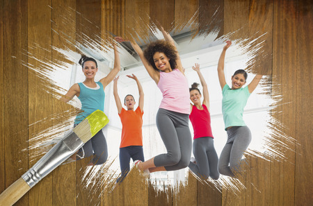Composite image of fitness class at the gym with paintbrush dipped in yellow against wooden surface with planks photo