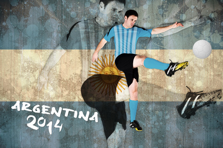 Football player in blue kicking against argentina flag in grunge effect photo