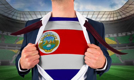 Businessman opening shirt to reveal costa rica flag against large football stadium with brasilian fans photo