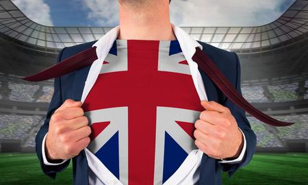Businessman opening shirt to reveal union jack flag against large football stadium under spotlights photo