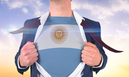 Businessman opening shirt to reveal argentina flag against beautiful orange and blue sky photo