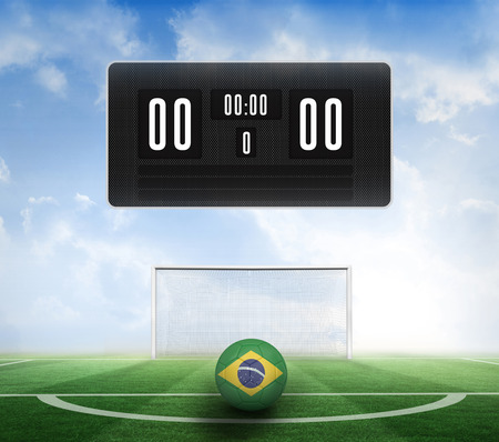 Black scoreboard with no score and football against football pitch under blue sky photo