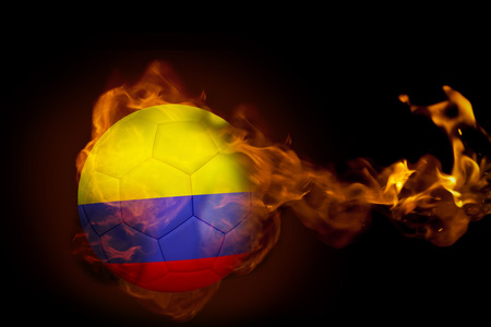 Composite image of fire surrounding colombia ball against black photo