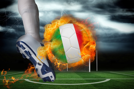 Football player kicking flaming italy flag ball against football pitch under stormy sky photo