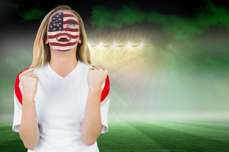 Excited fan in usa face paint cheering against football pitch under green sky and spotlights photo