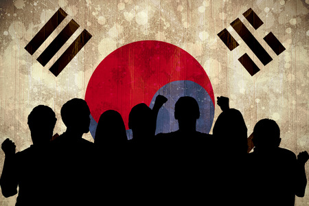 Silhouettes of football supporters against korea republic flag in grunge effect