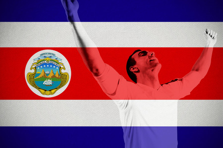Excited football fan cheering against costa rica national flag photo