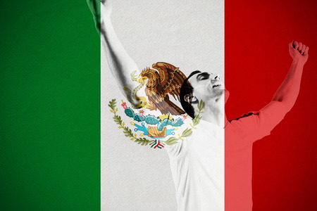 Excited football fan cheering against mexico national flag photo