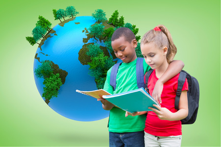 Cute pupils reading against green vignette with globe photo