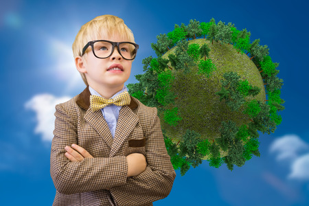 Cute pupil dressed up as teacher against bright blue sky with clouds with globe photo