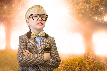 Cute pupil dressed up as teacher  against trees and meadow in the park photo
