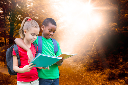 Composite image of cute pupils reading against forest trail photo
