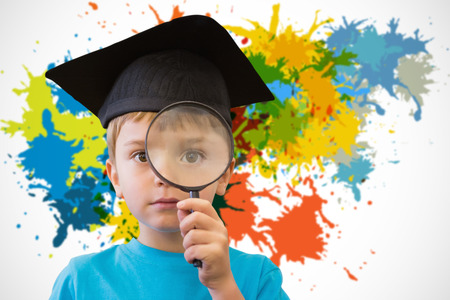 schoolkid search: Cute pupil looking through magnifying glass against white background with paint splashes Stock Photo