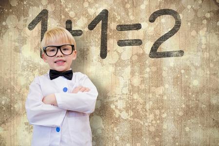 Cute pupil dressed up as teacher against paint splattered paper photo
