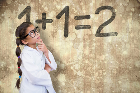 Cute pupil dressed up as scientist  against wooden surface with planks photo