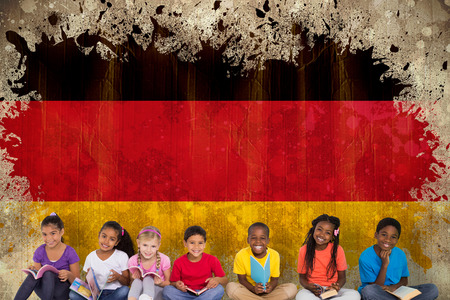 Elementary pupils reading books against germany flag in grunge effect photo