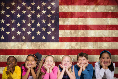 Cute pupils smiling at camera against usa flag in grunge effect photo
