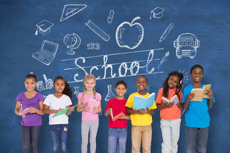 Elementary pupils reading books against blue chalkboard with back to school message photo