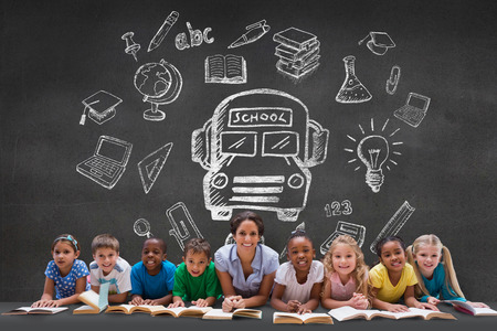 Cute pupils smiling at camera with teacher against black wall with school doodles photo
