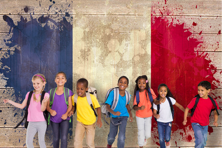 early childhood: Elementary pupils running against france flag in grunge effect Stock Photo