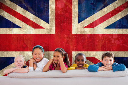 Cute pupils smiling at camera against union jack flag in grunge effect photo