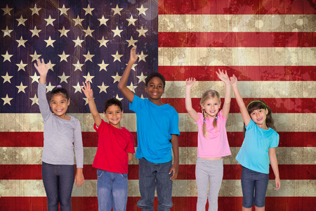 early: Elementary pupils smiling and waving against usa flag in grunge effect