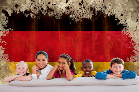 Cute pupils smiling at camera against germany flag in grunge effect photo