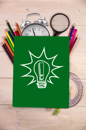 Light bulb with exclamation mark against students desk with green page photo