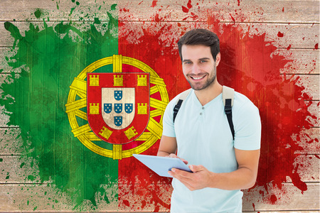 Student using tablet pc against portugal flag in grunge effect photo