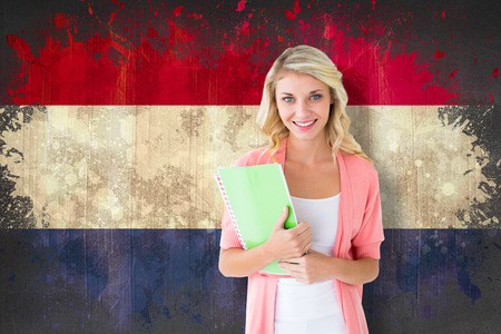 Young pretty student smiling against netherlands flag in grunge effect photo