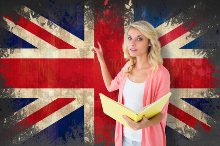 Young pretty student pointing and reading against union jack flag in grunge effect photo