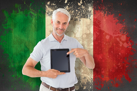 Mature student showing tablet pc against italy flag in grunge effect photo