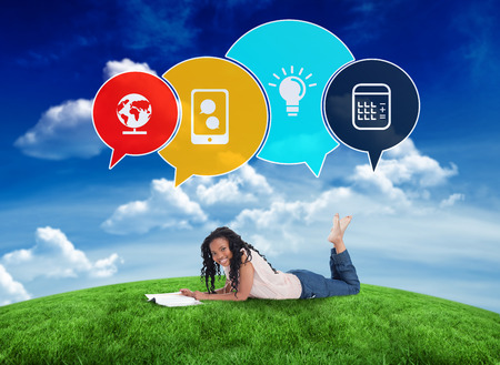 Composite image of happy student with speech bubbles against green field under blue sky photo