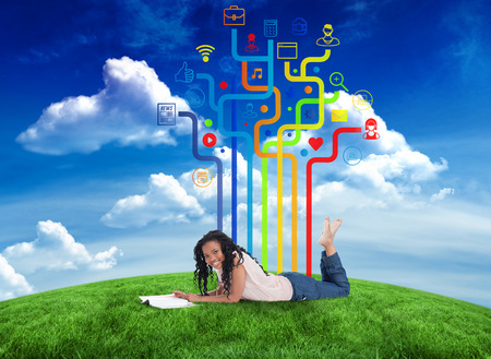 Composite image of happy woman with app icons against green field under blue sky photo