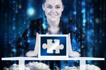Businesswoman sitting at desk showing tablet against lines of blue blurred letters falling photo