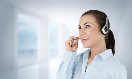 call center agent: Chiamare il centro agente guardando verso l'alto mentre parla contro luminoso corridoio bianco con colonne Archivio Fotografico