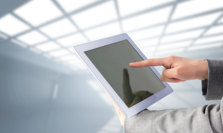 scrolling: Businesswoman using a tablet pc against white room with windows at ceiling