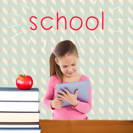 The word school and cute girl using tablet against red apple on pile of books photo