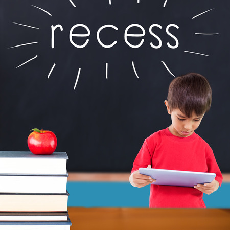 recess: The word recess and cute boy using tablet against red apple on pile of books in classroom