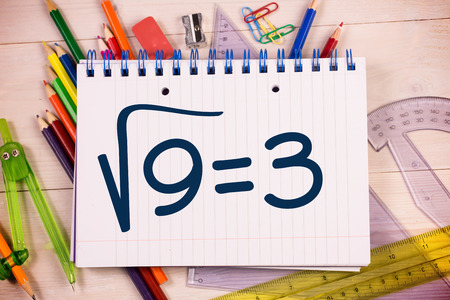 square root: Square root of three on notepad against students desk Stock Photo
